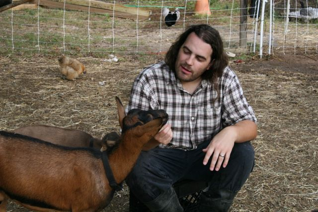A man, a goat, and some chickens.